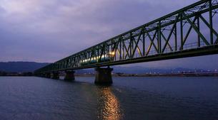 鉄橋を渡ってきた列車のライトが水面を照らしたの写真素材 [FYI00247200]