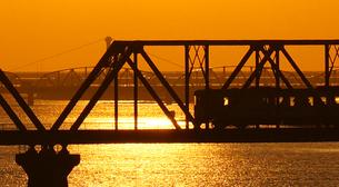 オレンジ色に輝く水面と列車の写真素材 [FYI00247214]