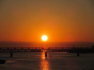綺麗な朝日と鉄橋を通過していく列車の写真素材 [FYI00247223]