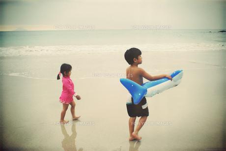 海岸を並んで歩く少年少女の写真素材 [FYI00250638]
