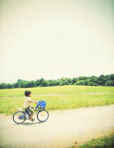 高原を自転車で走る少年の写真素材 [FYI00250647]