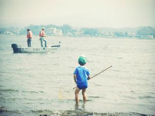 湖で魚を探す少年の写真素材 [FYI00250657]