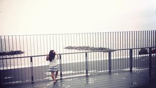 柵越しに海を眺める女の子の写真素材 [FYI00250658]
