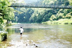 川で魚を探し歩く少年の写真素材 [FYI00250666]