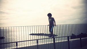 柵から海を眺める少年の写真素材 [FYI00250669]