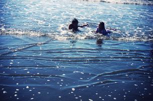 波打ち際で寝転んで遊ぶ子供たちの写真素材 [FYI00250690]
