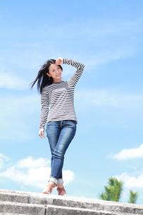 青空を背景に眩しそうな若い女性の写真素材 [FYI00253278]