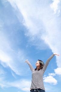 青空で伸びをする黒髪の若い女性の写真素材 [FYI00253282]