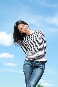 青空を背景に笑顔の若い女性の写真素材 [FYI00253286]