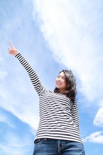 青空を背景に指を指す若い女性の写真素材 [FYI00253295]