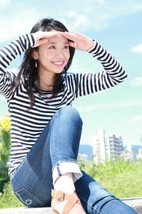 青空を背景に眩しそうな若い女性の写真素材 [FYI00253311]