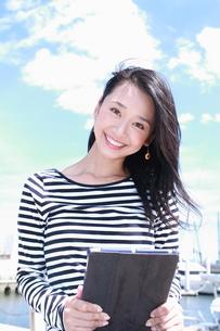 青空を背景にタブレット端末と若い女性の写真素材 [FYI00253312]