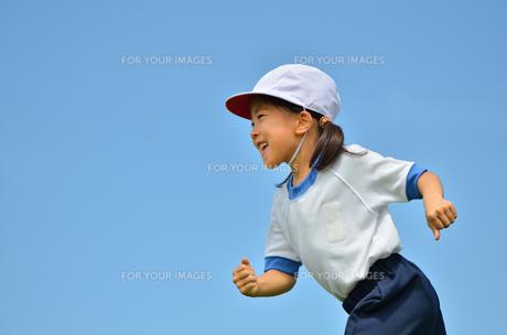 青空で走る女の子(体操服)の写真素材 [FYI00260644]