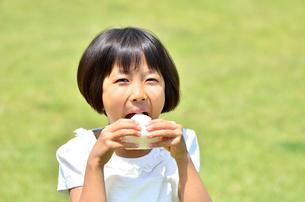 芝生広場でおにぎりを食べる女の子の写真素材 [FYI00260655]