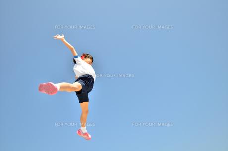 青空でジャンプする女の子(体操服)の写真素材 [FYI00260682]