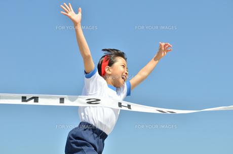 青空で走る女の子(体操服、ゴールテープ)の写真素材 [FYI00260686]