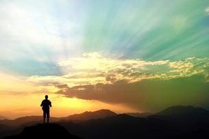 山頂に立つ男性と夕日の写真素材 [FYI00262777]
