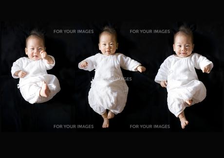 黒バックでポーズする3人の赤ちゃんの写真素材 [FYI00263123]