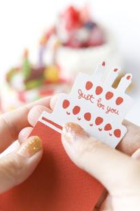 バースデーケーキとメッセージカードを持つ手の写真素材 [FYI00263425]