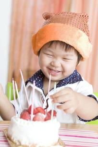 バースデーキャンドルを挿す嬉しそうな子供の写真素材 [FYI00263426]