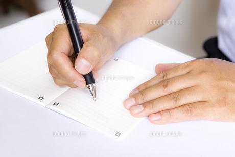 手帳を書く手元の写真素材 [FYI00263433]