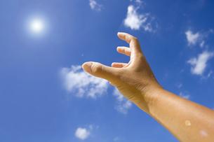 太陽を掴もうとする手の写真素材 [FYI00263514]