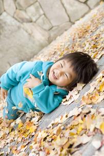 落ち葉に寝転んで嬉しそうな子供の写真素材 [FYI00263785]