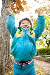 落ち葉とはしゃぐ子供の写真素材 [FYI00263791]