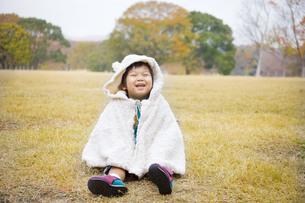 芝生に座って笑う子供の写真素材 [FYI00263826]