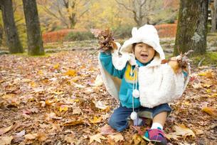 両手に落ち葉を持つ子供の写真素材 [FYI00263838]