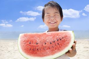 海で笑顔でスイカを持つ子供の写真素材 [FYI00264412]