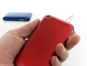 赤のスマートフォンを持つ手の写真素材 [FYI00268892]