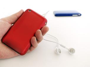 赤のMP3プレーヤーを持つ手の写真素材 [FYI00268900]