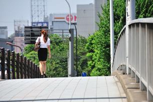 橋の上を歩くビジネスウーマンの写真素材 [FYI00270342]
