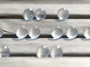 木のベンチに転がるガラス玉の写真素材 [FYI00271260]