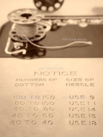 アンティークミシンの上のボビンと説明書きの写真素材 [FYI00278113]