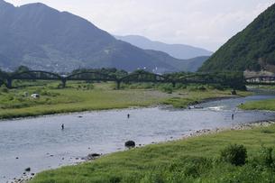 土木遺産の昭和橋と釣り人達の千曲川の写真素材 [FYI00278401]