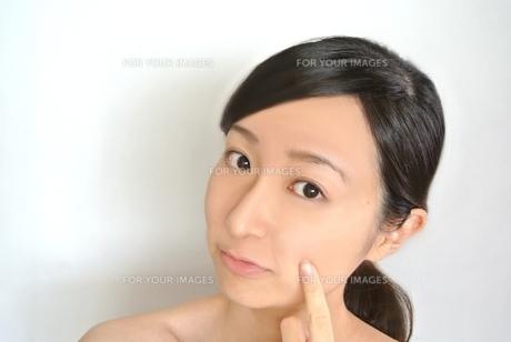 頬を指す女性の写真素材 [FYI00281025]