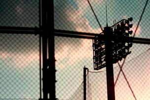 野球場のネット越しに見るグランドのナイター用照明の写真素材 [FYI00290099]