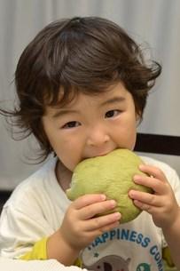 メロンパンを頬張る子供の写真素材 [FYI00299977]