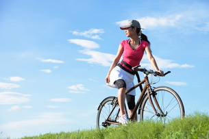 土手と自転車に乗る女性の写真素材 [FYI00307596]