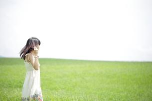 夏の草原に佇む女性の写真素材 [FYI00307599]