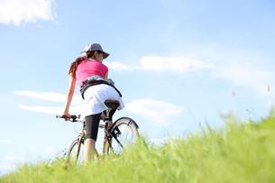 土手を走る女性と自転車の写真素材 [FYI00307612]