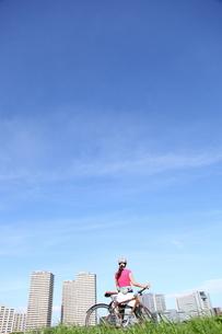 自転車通勤をする若い女性の写真素材 [FYI00307620]