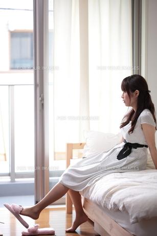 部屋で退屈そうな若い女性の写真素材 [FYI00307622]