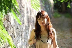 沖縄の石垣の道を散歩する20代女性の写真素材 [FYI00307627]