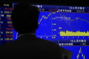 株価ボードを見る男性の写真素材 [FYI00307628]