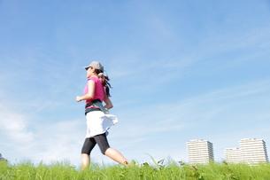 土手をジョギングする若い女性の写真素材 [FYI00307629]
