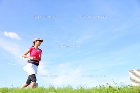 土手をジョギングする若い女性の写真素材 [FYI00307630]