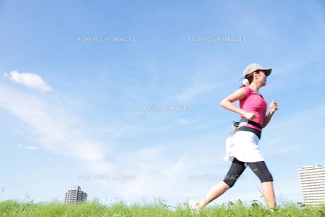 土手をジョギングする若い女性の写真素材 [FYI00307631]